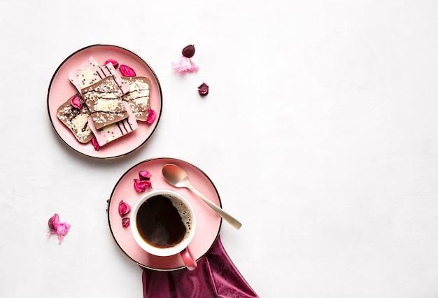 Coffee mug and pink chocolate on pink plates