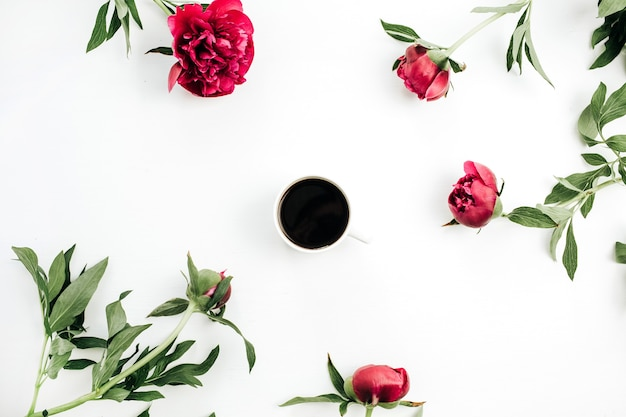 Coffee mug and pink peonies flowers on white surface