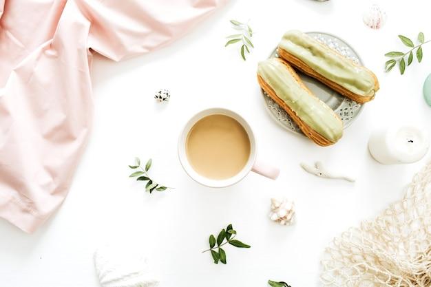 白い背景にコーヒー マグ、ピスタチオ ケーキ、ピンクの毛布、ひも袋、貝殻。フラットレイ、トップビュー