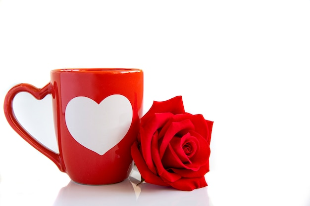 A coffee mug and a red rose