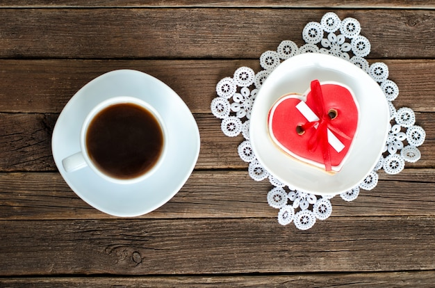 Coffee mug, saucer with red heartshaped gingerbread on the old wooden background. top view
