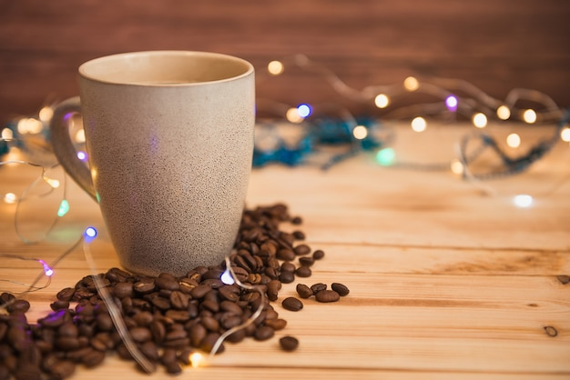 Coffee mug and scattered coffee beans, christmas lights on background, selective focus.