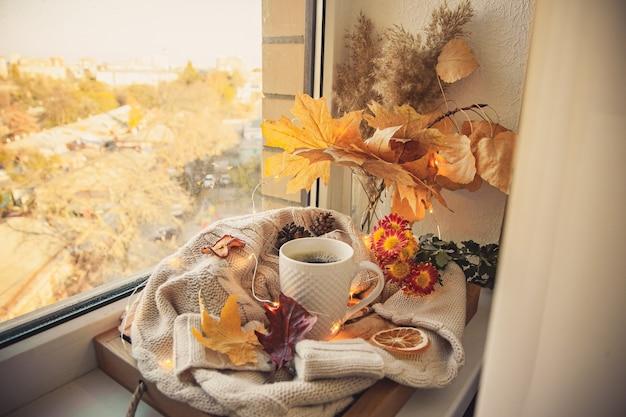 Кофейная кружка в окружении свитеров и осеннего декора