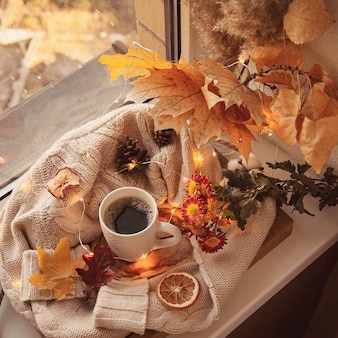 Coffee mug surrounded by sweaters and autumn decor