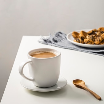 Coffee mug on table with cookies on plate and spoon