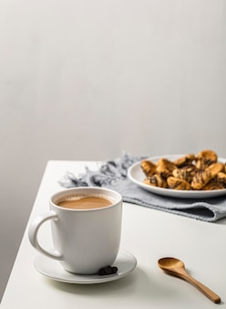 Coffee mug on table with plate of cookies