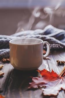 木製のテーブルに秋のカエデの葉と女性のウールのスカーフとコーヒーマグ