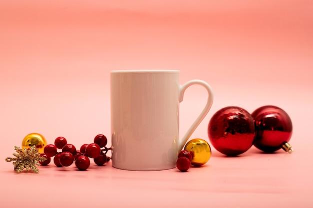 Кружка кофе с рождественскими украшениями вокруг нее на розовом фоне
