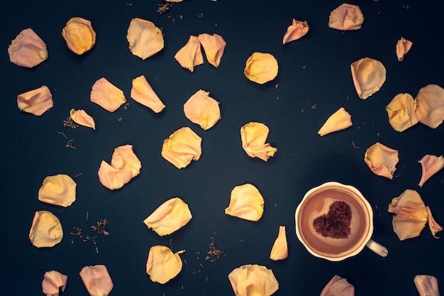 Кофейная кружка со сливками и корицей в форме сердца с розовыми лепестками цветов на темно-синем фоне. плоская планировка. виньетирование.