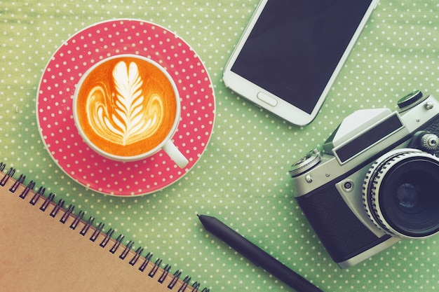 거품과 사진 카메라에 그림이있는 커피 잔