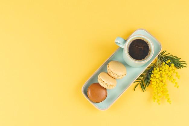 黄色の背景にマカロンと黄色の花の装飾が施されたコーヒーマグ。スペースをコピーします。上面図。春のコンセプト。