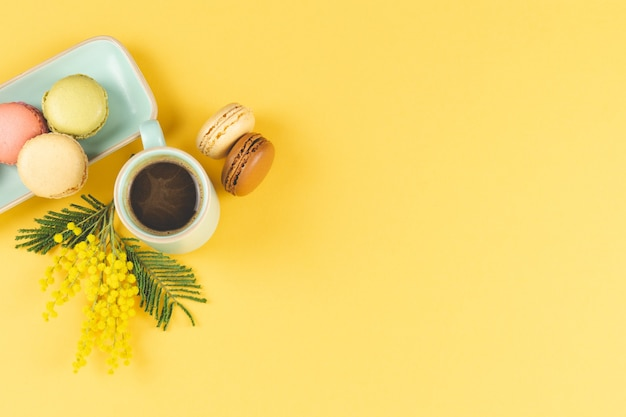 Coffee mug with macarons and yellow flowers decoration on yellow. top view.