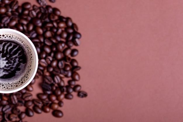 石の背景にロースト豆とコーヒーマグ。コピースペースのある上面図
