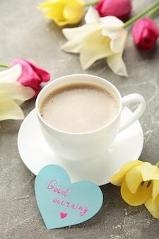 Кофейная кружка с цветами тюльпана и нотами доброе утро на серой поверхности, завтрак в день матери или женский день