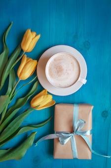黄色のチューリップの花と上から青い素朴なテーブルにプレゼントボックス、母の日に朝食とコーヒー・マグ