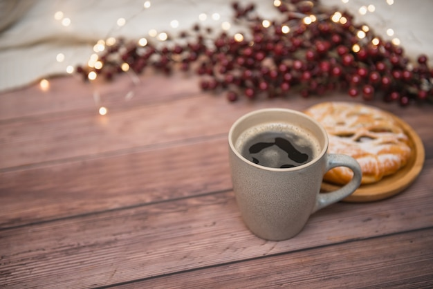 Coffee mug on wooden background, appetizing bun and christmas lights, selective focus.