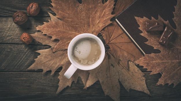 Coffee mug on wooden table autumn theme