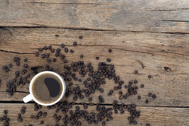 コーヒーマグとコーヒー豆は机の上にあります
