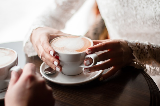 Coffee mugs of cappuccino in the hands  couple