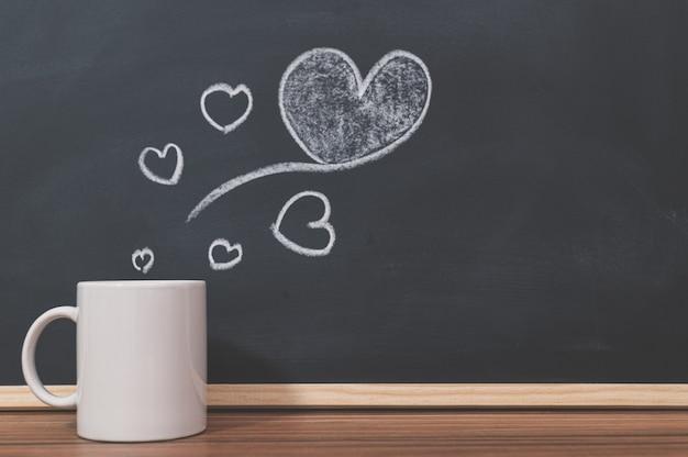 Coffee mugs and heart shapes on the blackboard