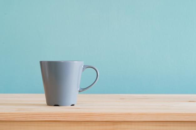 コーヒーマグは茶色の木製の机と青い壁紙の上に置きます