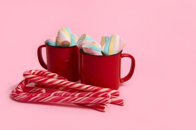 ピンク色の背景にマシュマロとキャンディケインとコーヒーマグ。デザートとクリスマスの温かい飲み物。ホットチョコレート、コーヒーココアのカップ。新年、メリークリスマスの休日のお祝い