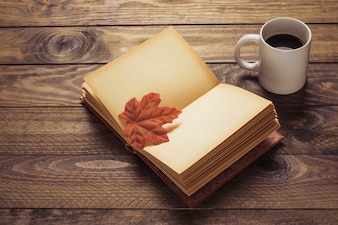 Coffee near book with leaf