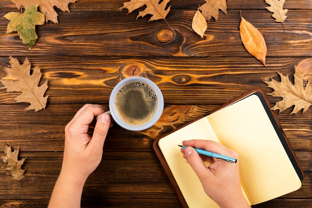 Coffee and notebook on autumn leaves background