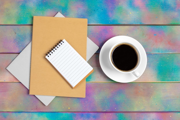 Coffee, notepad and corporate documents, top view