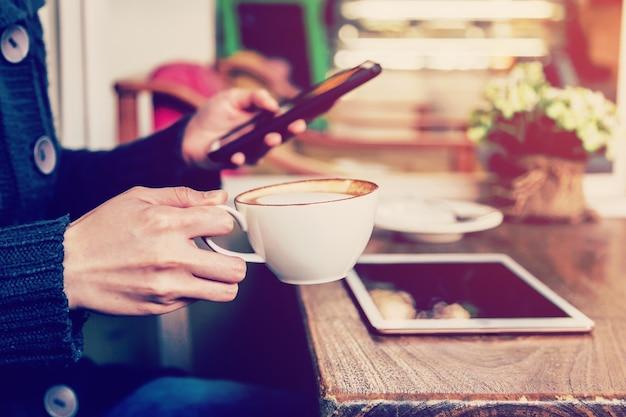 손에 커피와 빈티지 톤 커피 숍에서 스마트 폰 재생.