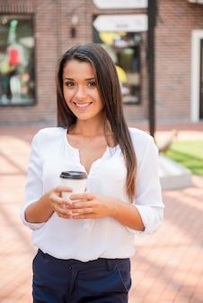 이동 중 커피. 야외에 서서 커피잔을 들고 웃고 있는 아름다운 젊은 여성