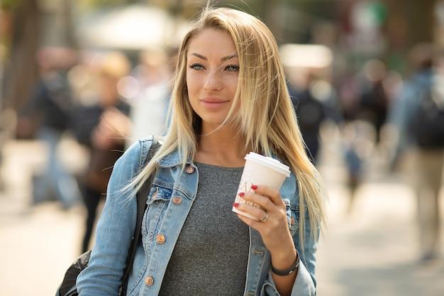 外出先でのコーヒー。コーヒーカップを持って、通りを歩きながら笑顔の美しい若い女性。