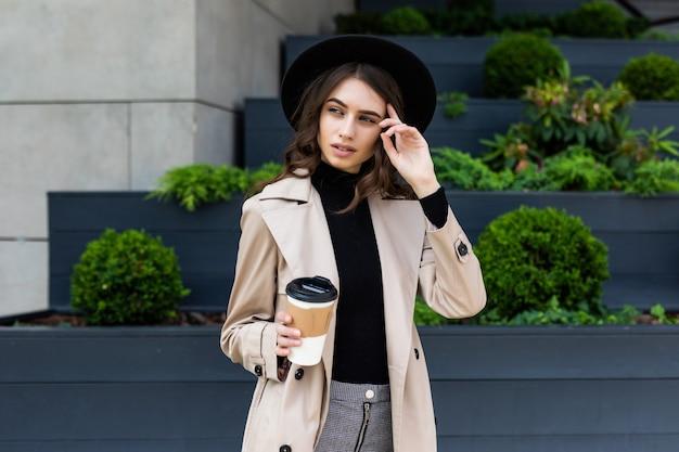 이동 중에도 커피. 커피 컵을 들고 거리를 따라 걷는 동안 웃 고 아름 다운 젊은 여자