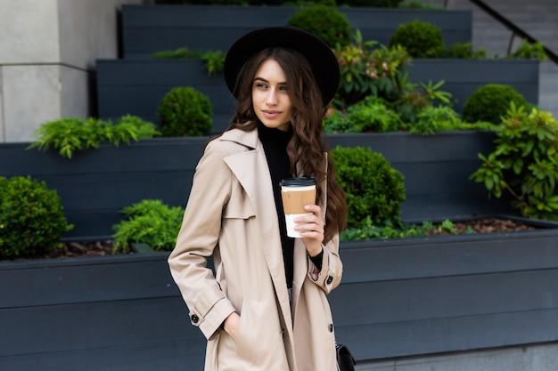 外出先でのコーヒー。コーヒーカップを持って、通りを歩きながら笑顔の美しい若い女性
