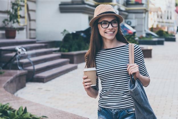 이동 중에도 커피. 커피잔을 들고 거리를 걷는 동안 웃고 있는 아름다운 젊은 여성