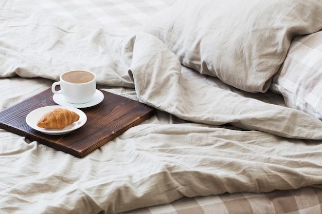 寝室のベッドの上のトレイにコーヒー