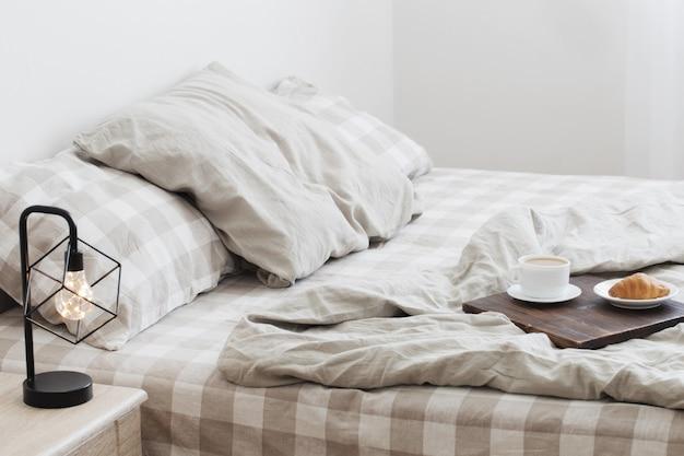 Кофе на подносе на кровати в спальне