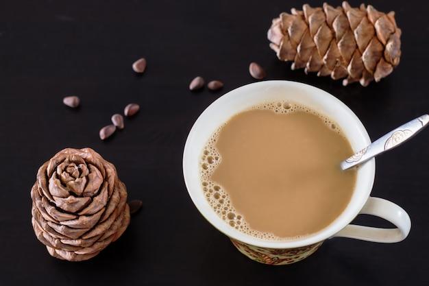 松の実と杉ビーガンミルクのコーヒーまたはミルクティーチャイ。黒い木製の背景とシベリア杉松の円錐形。上面図。セレクティブフォーカス。