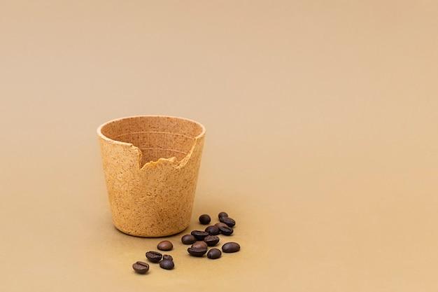 Чашка кофе или чая с жареными кофейными зернами на бежевом фоне съедобных чашек как новый тренд без отходов