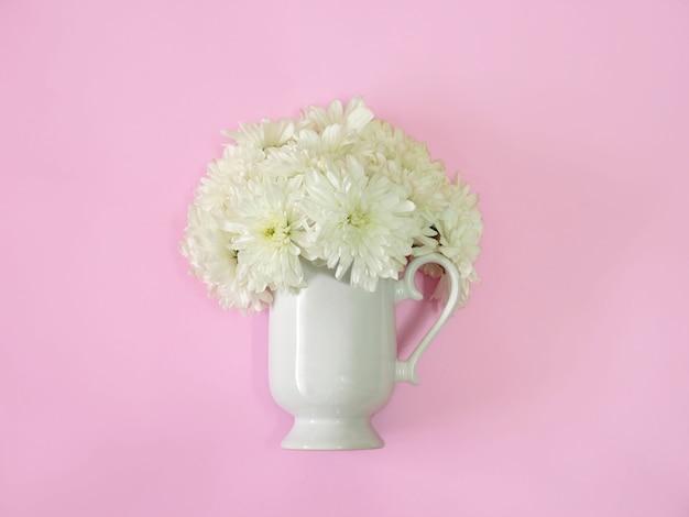 ピンクの背景に白い花が入ったコーヒーまたはティーカップ。最小限のフラットレイ