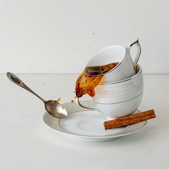 白い背景の磁器カップからこぼれるコーヒーまたは紅茶。正方形の画像。朝食のコンセプト