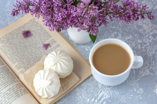 ミルクとマシュマロを入れたコーヒーまたは紅茶。一杯のコーヒーで庭で本を読んでください。ライラック色の花のロマンチックな静物。