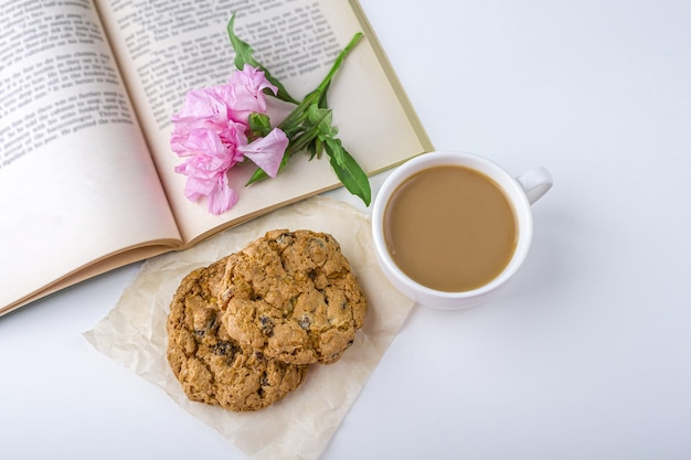 コーヒーまたは紅茶とミルクとオート麦のクッキー。庭で春夏の古い本とおやつを読む