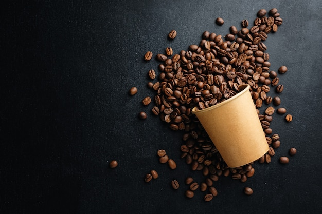 커피 또는 제로 폐기물 개념. 어두운 배경에 종이 컵에 커피 콩입니다.