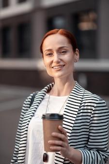 屋外でコーヒー。笑顔で彼女の前を見ながらコーヒーを持って喜んでいる白人の若い女性の正面図