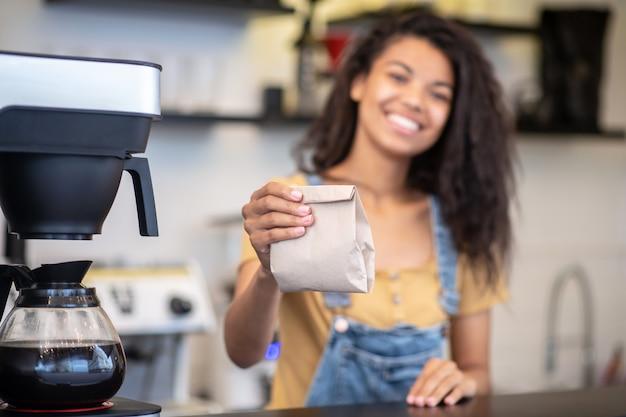 コーヒーパッケージ。カフェのカウンターの後ろに立っている陽気な長髪のバリスタ女性の伸ばした手に小さな紙袋