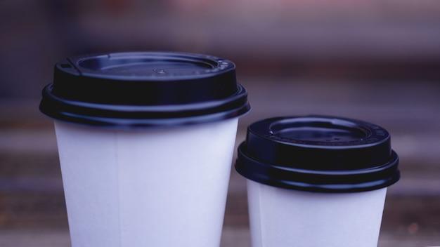 コーヒーペーパークラフトカップは、ぼやけた背景の木製の表面に立っています。テキストまたはロゴの場所。