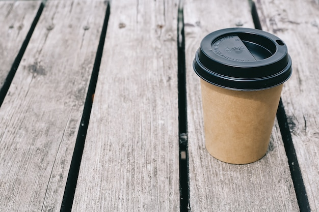 Coffee paper cup on brown wooden background. copyspace