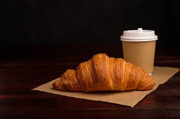 Coffee in paper cup and croissant on wooden table