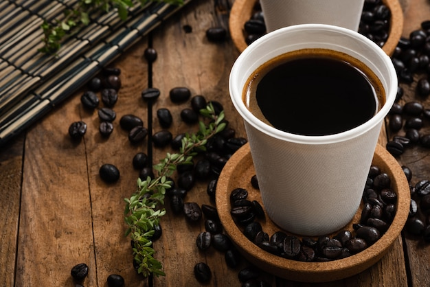 Coffee in paper cup on wood